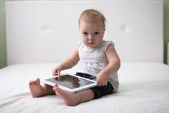 Säuglingskinderbabykleinkind, das digitalen Tablettenbaut. sitzt und schreibt Lizenzfreies Stockbild