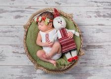 Säuglingsmädchen im ukrainischen Kostüm schlafend mit einem Spielzeughasen Stockbilder