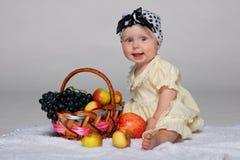 Säuglingsmädchen nahe dem Korb mit Gemüse Stockbild