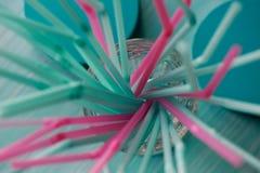 Sugrör för drinkar i rosa färger och turkossignaler Två färgar Pastellfärgade skuggor Defocusing Arkivbilder