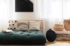 Sugrörhandväskor bredvid den stilfulla svarta vasen och den utsmyckade soffan med kuddar som göras av futonen, svart affisch på v royaltyfria foton