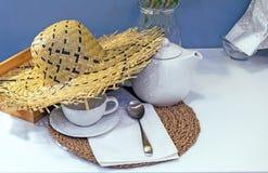 Sugrörhatt på tabellen med teanordningar arkivfoto