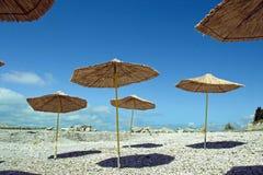 Sugrörparaplyer med skugga på stranden Arkivfoto