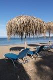 Sugrörparaplyer och sunbeds på en sandig strand, Korfu, Grekland Royaltyfri Fotografi