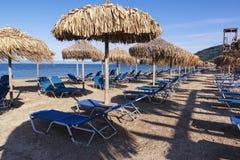 Sugrörparaplyer och sunbeds på en sandig strand, Korfu, Grekland Fotografering för Bildbyråer