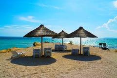 Sugrörparaplyer på den Adriatiska havet kusten Arkivbild