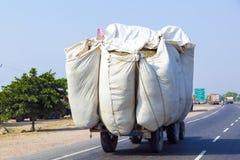 Sugrörtransport med traktoren på landsvägen Arkivfoto