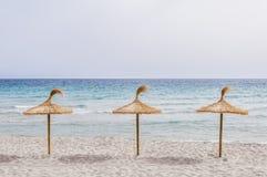 Sugrörparaplyer på sandstranden Arkivfoton