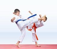 Sui bambini delle stuoie di un rosso i ragazzi stanno battendo le gambe di scossa Fotografia Stock