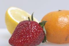 Sui frutti e sulle bacche di bugia della tavola: fragole, limone e mandarino Fotografie Stock