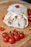 Sui piccoli pomodori ciliegia della priorità alta sulla fine di legno marrone del fondo su Burrito vegetariano con le verdure su  Fotografia Stock Libera da Diritti