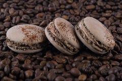 Sui precedenti dei biscotti di gusto del cioccolato di bugia dei chicchi di caffè, macaron immagini stock libere da diritti