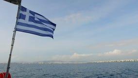 Sui precedenti del paesaggio delle montagne e del mar Mediterraneo, la bandiera blu e bianca della Grecia è archivi video