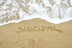 SUICIDAIRE écrit sur le sable images stock