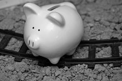 Suicidal Bank. A sad looking empty piggy bank sitting on railroad tracks stock images