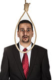 Suicidal businessman contemplating hanging. Standing looking at a hangmans noose royalty free stock photography