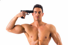 Suicidal man pointing a gun at his head. Suicidal attractive young man in an unbuttoned shirt standing with a serious expression pointing a gun at his head royalty free stock photos