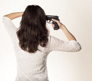 Suicidal woman. Back view of a girl holding a gun on her temple royalty free stock photography