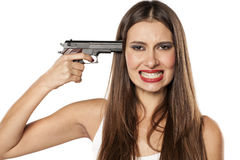 Suicidal woman. Desperate young woman pointing a gun at her head royalty free stock photos