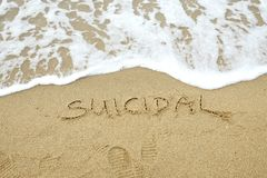 SUICIDAL written on sand. Nearly washed away by the wave stock images