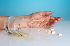Suicide. Hand of a person who comitted suicide with sleeping tablets and alcohol Royalty Free Stock Photography