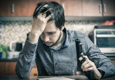 Suicide attempt. Sad man with pistol in hand is writting message Royalty Free Stock Photo