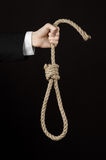 Suicide and business topic: Hand of a businessman in a black jacket holding a loop of rope for hanging on black isolated Stock Photo