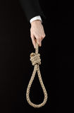 Suicide and business topic: Hand of a businessman in a black jacket holding a loop of rope for hanging on black isolated Royalty Free Stock Photos
