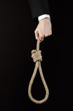Suicide and business topic: Hand of a businessman in a black jacket holding a loop of rope for hanging on black isolated Royalty Free Stock Images