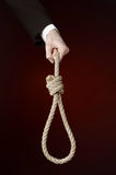 Suicide and business topic: Hand of a businessman in a black jacket holding a loop of rope for hanging on dark red isolated Stock Image