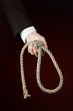 Suicide and business topic: Hand of a businessman in a black jacket holding a loop of rope for hanging on dark red isolated Stock Photos