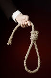 Suicide and business topic: Hand of a businessman in a black jacket holding a loop of rope for hanging on dark red isolated Royalty Free Stock Images