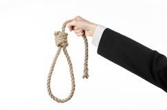 Suicide and business topic: Hand of a businessman in a black jacket holding a loop of rope for hanging on white isolated Stock Photo