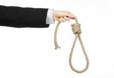 Suicide and business topic: Hand of a businessman in a black jacket holding a loop of rope for hanging on white isolated stock image