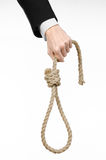 Suicide and business topic: Hand of a businessman in a black jacket holding a loop of rope for hanging on white isolated Royalty Free Stock Images