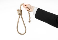 Suicide and business topic: Hand of a businessman in a black jacket holding a loop of rope for hanging on white isolated Royalty Free Stock Photo