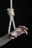 Suicide and depression topic: human hand hanging on rope loop on a black background Royalty Free Stock Images