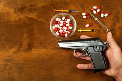 Suicide by firearm. Hand holding pistol. A weapon in the palm of your hand. Drugs and depression. Drugs for mental illness. Suicide by firearm. Hand holding royalty free stock images