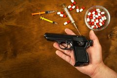 Suicide by firearm. Hand holding pistol. A weapon in the palm of your hand. Drugs and depression. Drugs for mental illness. Suicide by firearm. Hand holding royalty free stock photo