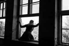 The suicide girl wants to jump out of the window. She is very close to do it royalty free stock images