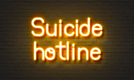 Suicide hotline neon sign on brick wall background. Stock Photo