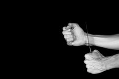 Suicide. Man want to commit suicide. By cutting his veins with knife. Low key image, isolated on black background. Black and white Stock Image