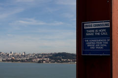 Suicide Prevention On The Golden Gate Bridge. A crisis counseling suicide prevention sign attached to a pillar on the Golden Gate Bridge with San Francisco in Stock Images