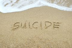 SUICIDIO scritto sulla sabbia immagini stock