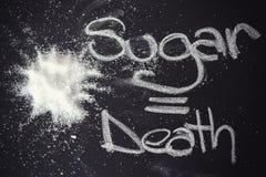 Suiker op zwart bord van hierboven Stock Afbeeldingen