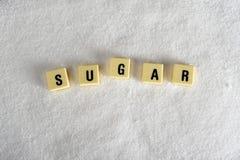 Suikerblokletters in kruiswoordraadsel over suikerstapel op korrelige witte suikertextuur worden geïsoleerd in zoet voedselmisbru Royalty-vrije Stock Foto
