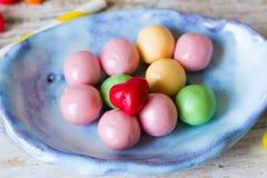 Suikergoed in een ceramische met de hand gemaakte plaat Stock Afbeelding