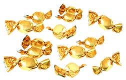 Suikergoed in gouden die folie op wit wordt geïsoleerd Stock Foto