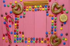 Suikergoed op een houten roze lijst stock foto