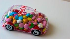 Suikergoed in stuk speelgoed auto - spaarpot stock fotografie